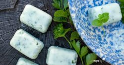 natural dog treats for fresh breath with fresh mint and parsley beside a blue stoneware bowl