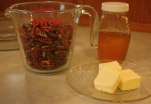 glass cup of pecans, butter, jar of honey