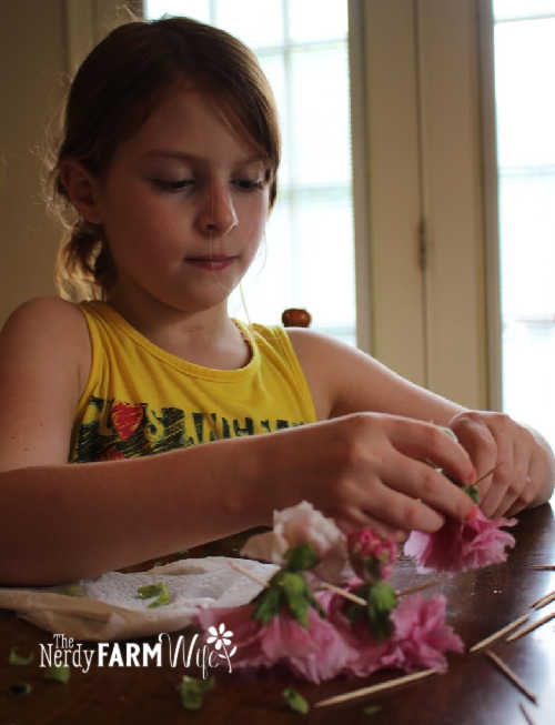girl with red hair and yellow shirt making old-fashioned dolls from hollyhock flowers