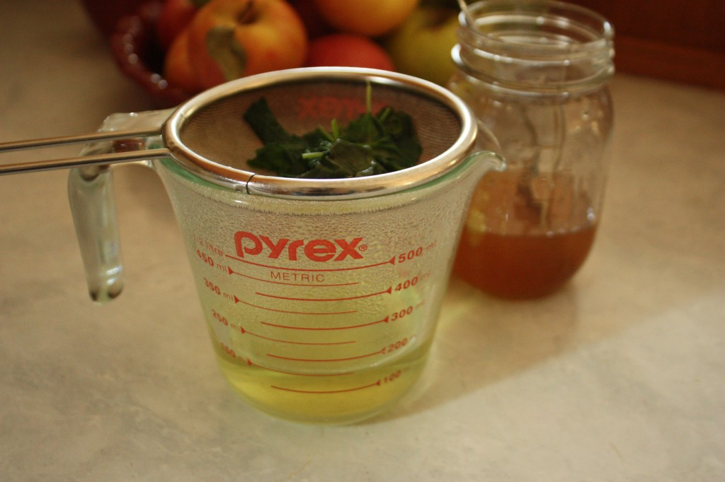 straining violet leaf infusion into a glass measuring cup
