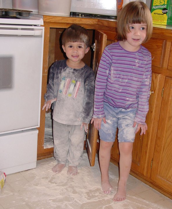 A little girl and boy standing in a kitchen