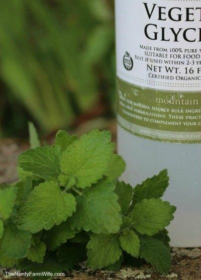 bottle of organic vegetable glycerin with fresh lemon balm leaves