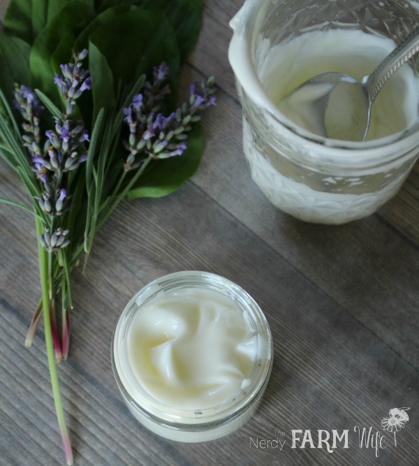 a fresh batch of lavender plantain lotion in a glass jar with fresh lavender and plantain sprigs on a wooden background