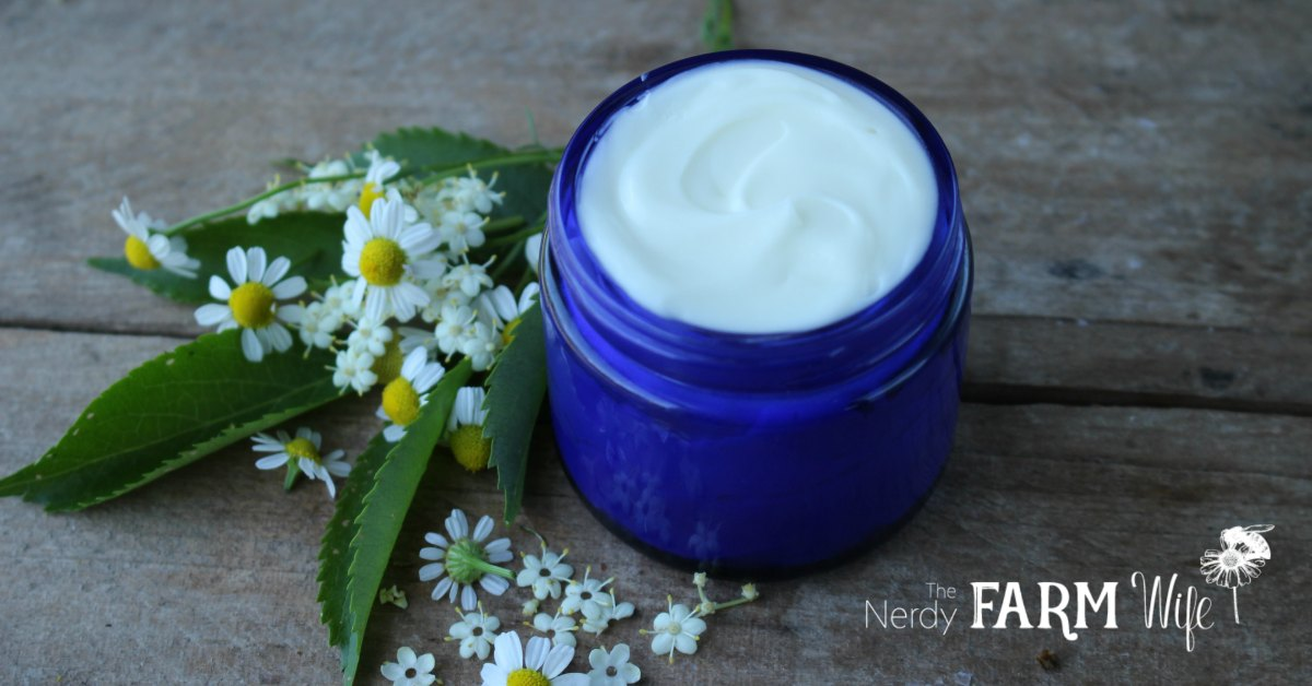 cobalt blue jar filled with face cream on a wooden background with fresh chamomile and elder flowers and leaves