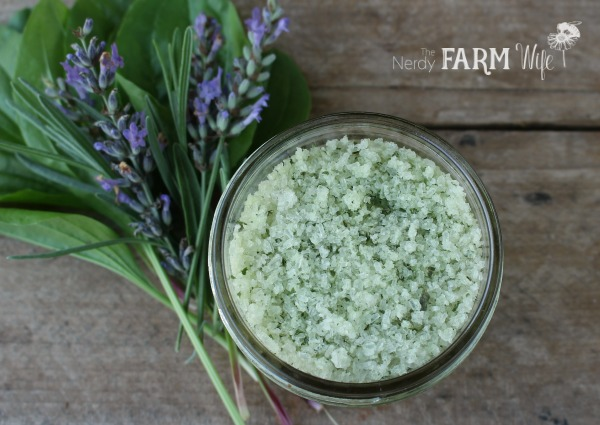 jar of lavender plantain bath salts on a wooden background with fresh sprigs of lavender flowers and plantain leaves