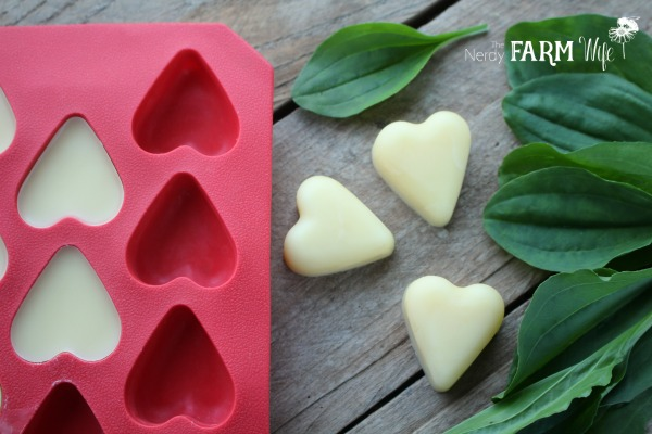 heart shaped plantain lotion bars on a wooden background with red silicone mold with heart shaped cavities