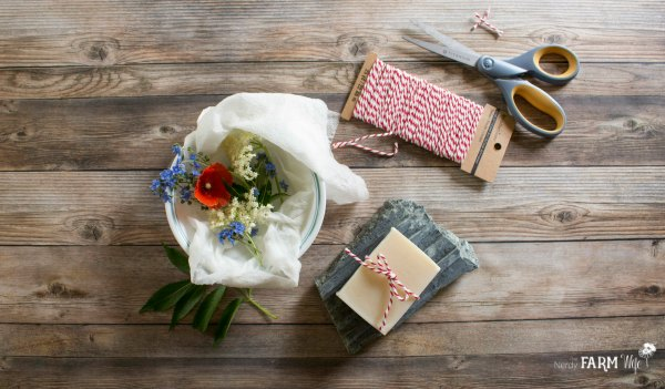 A wooden table with soap, string, and flowers