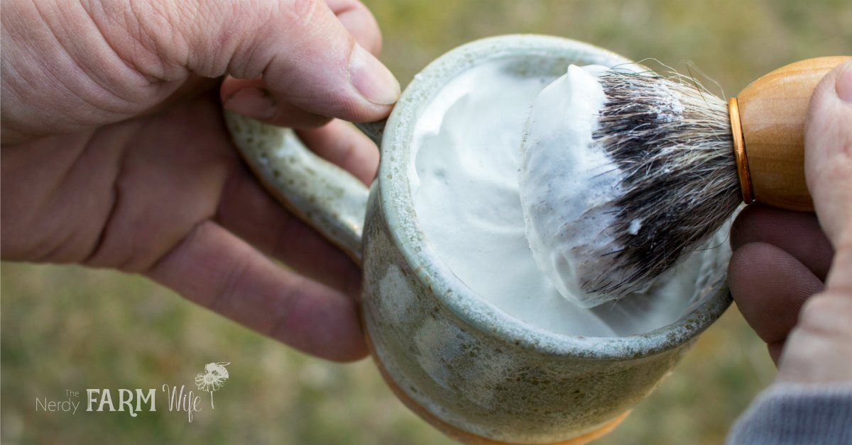 A mug of shaving soap and brush with foam
