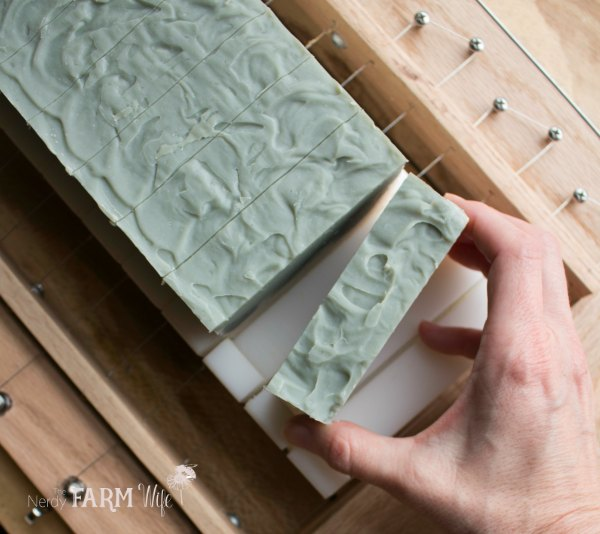 cutting handmade cold process soap with a wooden soap cutter