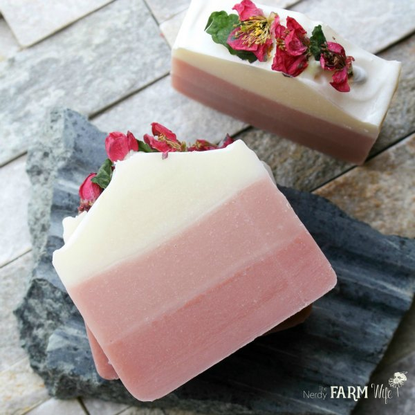 two bars of natural soap colored with pink clay