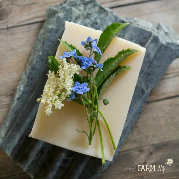 a bar of simple soap decorated with forget me not and elderflowers