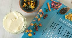 jar of flower infused body butter, pottery bowl of dried calendula, and Healing Herbal Infusions book