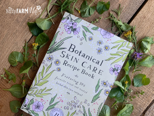 illustrated book of botanical recipes surrounded by fresh herbs