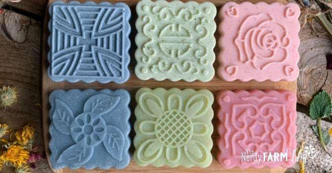 several square soaps with decorative tops in shades of pastel pink, green, and blue on a wooden background with dried flower decorations