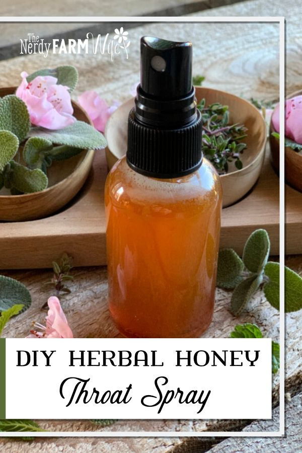 bottle of herbal honey throat spray surrounded by fresh peach blossoms, thyme, and sage leaves on a wooden background
