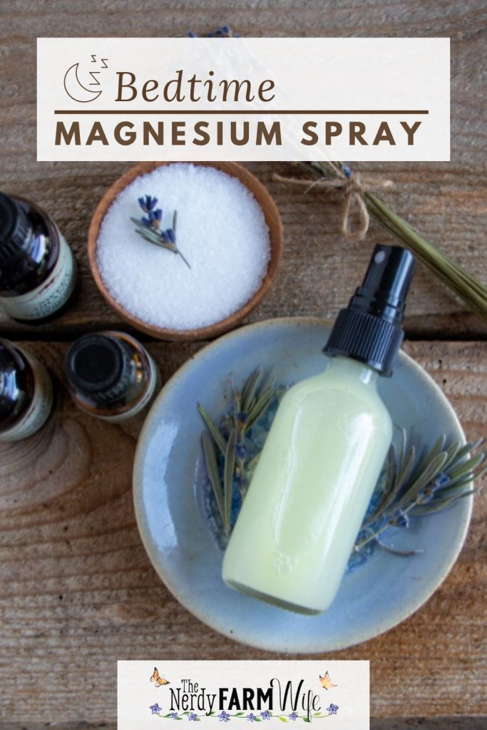 bottle of magnesium spray on a blue ceramic dish with dried lavender flowers, a small wooden bowl with magnesium salts, and small bottles of essential oils