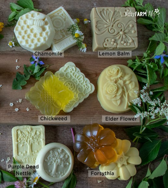 various melt and pour soaps on a wooden background surrounded by fresh flowers and herbs