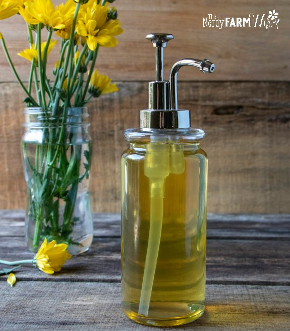 soap pump with calendula infused liquid soap on a wooden background with vase of yellow flowers in background