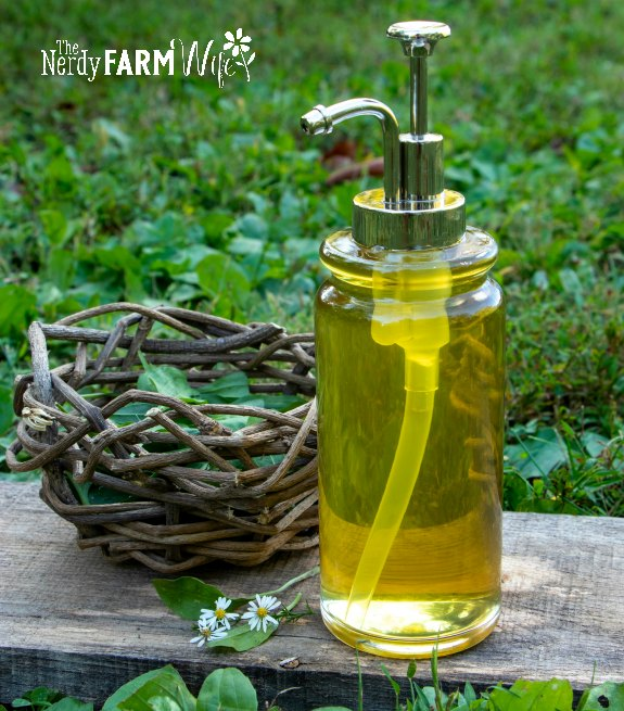 glass soap pump of herbal liquid soap on a wooden board and plantain leaf and grass covered ground