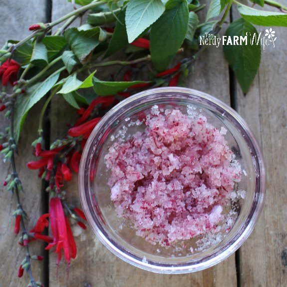 bowl of body scrub surrounded by fresh flowers
