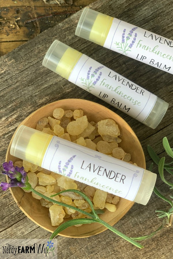 tubes of lip balm on a wooden background with bowl of resin and sprig of fresh lavender