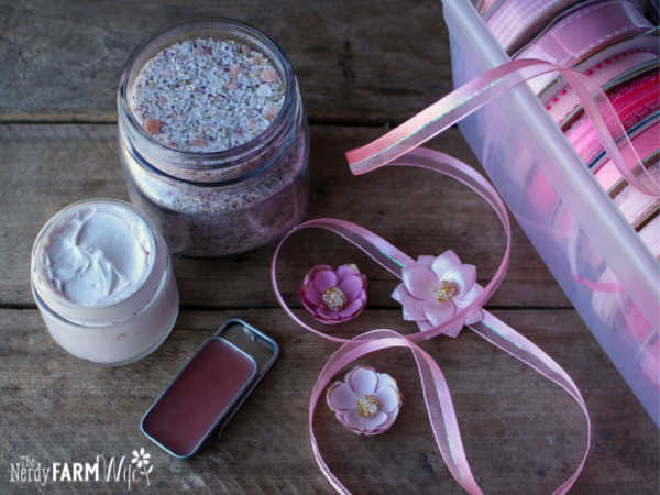 group of skin care products including lip balm, hand cream, bath soak, beside box of pink ribbons