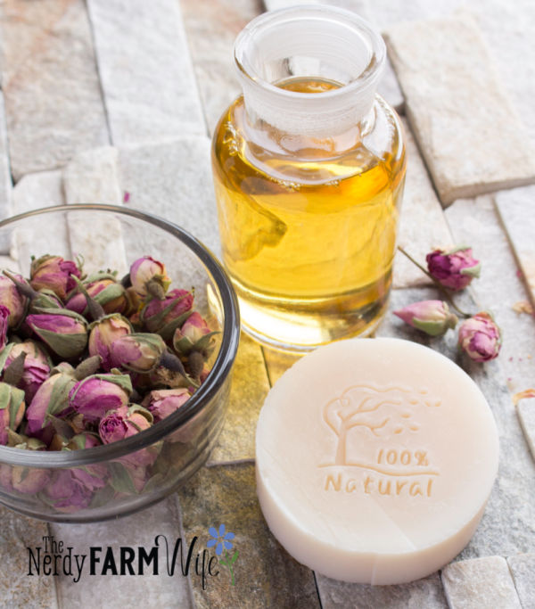 jar of agave nectar, dried rose buds, and round bar of soap on a rock background