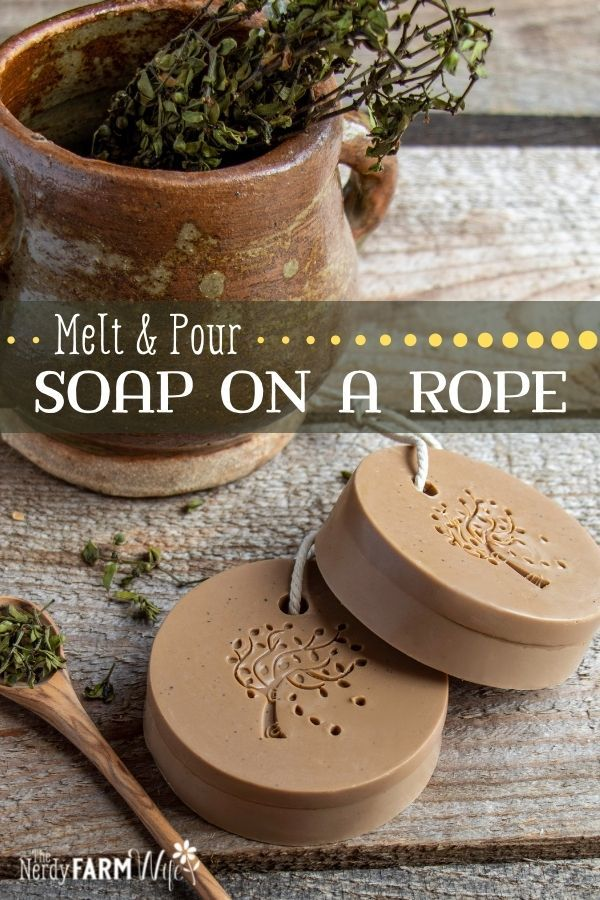 two bars of melt and pour soap on wooden background with chaparral herb