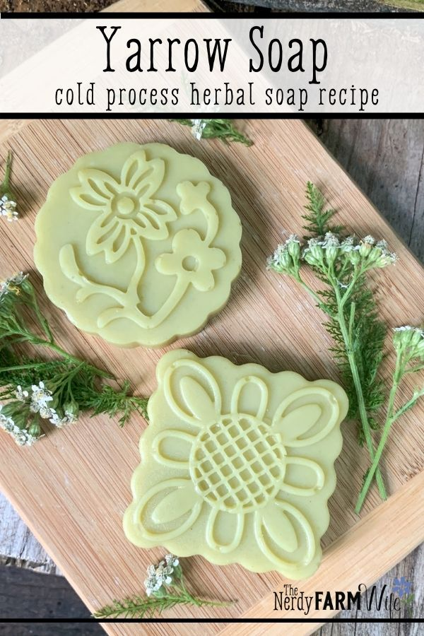 two decorative bars of soap on a bamboo cutting board with fresh yarrow flowers