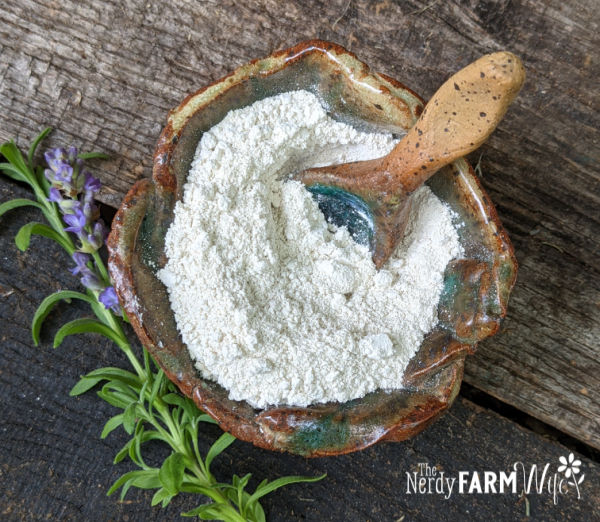 rustic bowl filled with white clay on a wooden background with sprigs of lavender flower and leaf