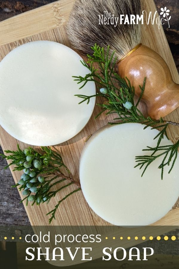round bars of soap on bamboo cutting board with fresh sprigs of cedar