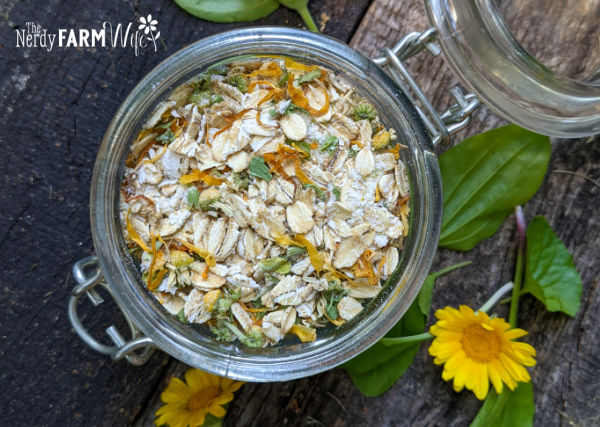 glass jar filled with bath soak made of oats, powdered milk, and dried calendula on wooden background