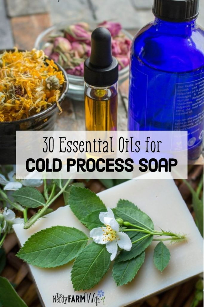 bottles of essential oil and a bar of soap with fresh leaves and flowers