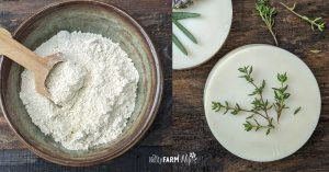 bowl of diatomaceous earth beside round bars of soap with fresh thyme and lavender on top