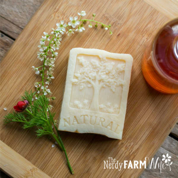"""bar of soap that says """"natural"""" on a wooden board with fresh flowers and bottle of wheat germ oil"""