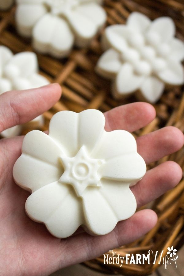 woman's hand holding flower shaped bar of castile soap